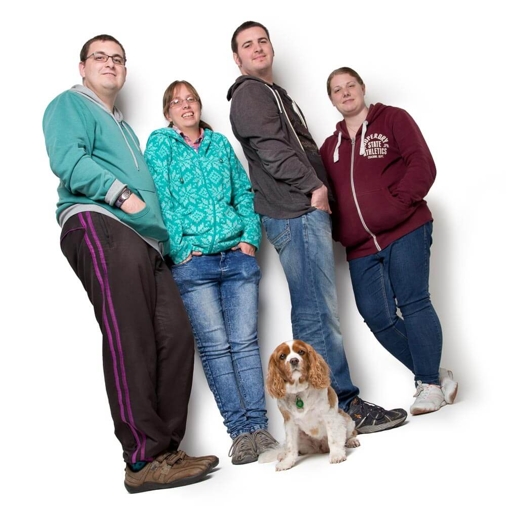 Portrait of four friends and their dog on a White Background